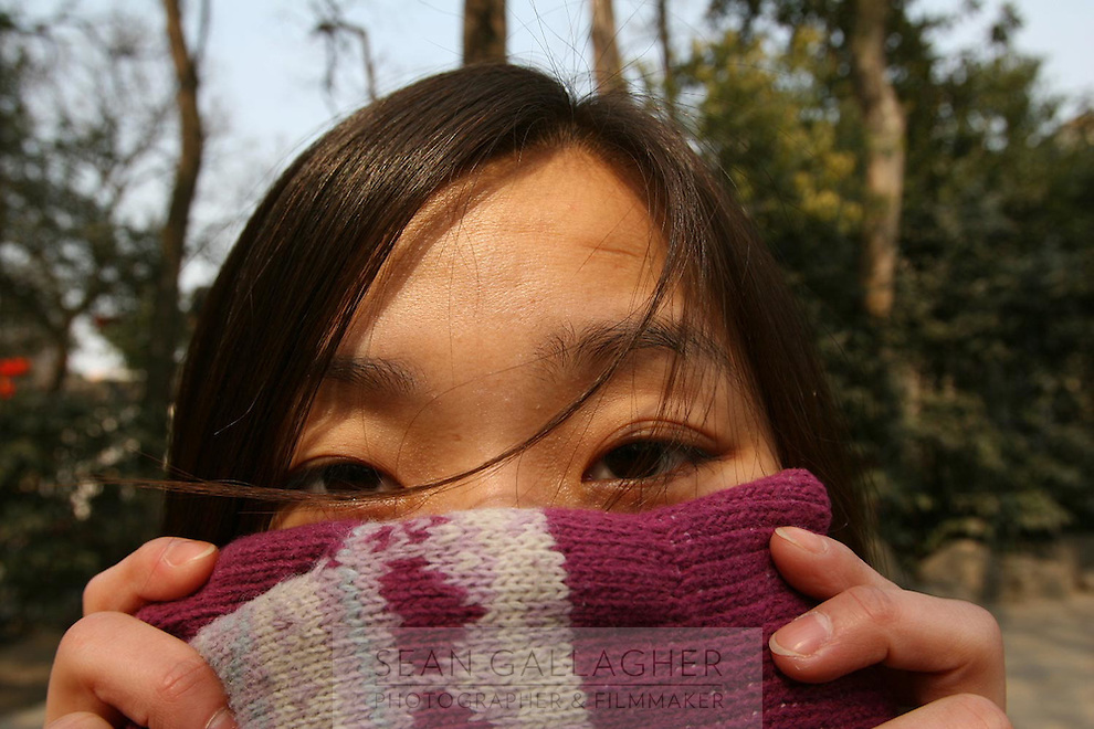 A Chinese woman hides her face with a colourful glove.<br /> <br /> To license this image, please contact the National Geographic Creative Collection:<br /> <br /> Image ID:  1933619<br />  <br /> Email: natgeocreative@ngs.org<br /> <br /> Telephone: 202 857 7537 / Toll Free 800 434 2244<br /> <br /> National Geographic Creative<br /> 1145 17th St NW, Washington DC 20036