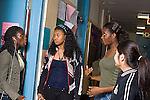 High school group of girls talking in corridor.