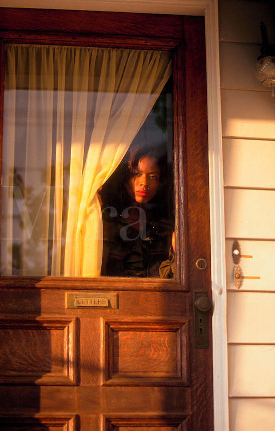 African American woman looking out the front door window of her home.