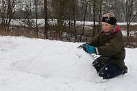 Kinder bauen einen Seehund, Robbe aus Schnee