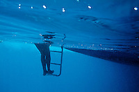 Bare legs descending underwater from the ladder of a boat, Maldive Islands.