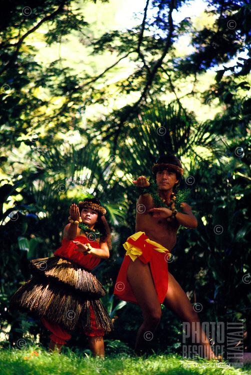A woman and man from Halau O Waimea perform hula kahiko (ancient/traditional hula) in an outdoor performance at the Moanalua Gardens on Oahu.
