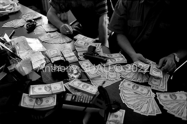 "Moscow, Russia .1995.Over $100,000 in ""black money"" is counted by men in a Moscow office. Guns are normally present with such sums of cash. Most of the money was recoved when a Razbourka was theatened. Tatoos are a gang related mark."