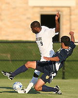 Bright Dike #9 of the University of Notre Dame is tackled by Julian Robles #3 of the University of Michigan during a men's NCAA match at the new Alumni Stadium on September 1 2009 in South Bend, Indiana. Notre Dame won 5-0.