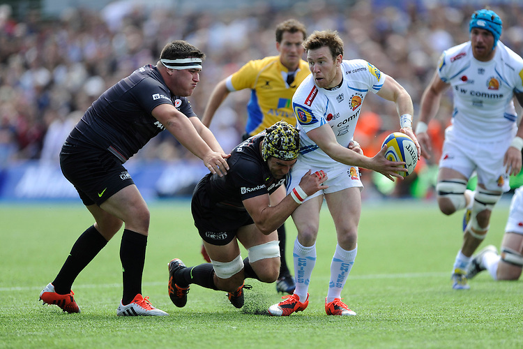 Will Chudley of Exeter Chiefs offloads as he is tackled by Kelly Brown of Saracens as Jamie George of Saracens supports