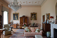 Two antique portraits of ladies of the hall flank an antique armoire in the pastel coloured living room