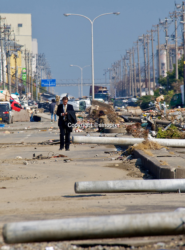 A Japanese salary man looks calm in the Sendai port area after the earthquake and tsunami that swept through the area, Sendai, Japan.  The earthquake, tsunami and nuclear fallout has meant that the March 11th quake was the most expensive natural disaster known to man..13 Mar 2011..