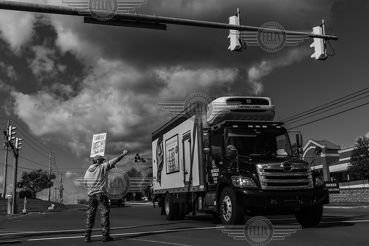 An employee of Mack Trucks, taking part in an industrial dispute, raises his fist as a vehicle passes where he stands on the road in front of the company's offices.