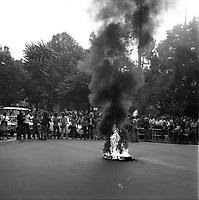 Carrefour de l'avenue d'Alsace-Lorraine et de la rue Lafayette. 5 septembre 1975. Scène de manifestation : au 1er plan feu et fumée noire (pneus) au milieu de la route ; au 2nd plan une rangée de personnes bloque la circulation venant de l'avenue d'Alsace-Lorraine, foule sur le trottoir ; en arrière-plan Square Charles de Gaulle. Cliché pris lors d'une manifestation contre le Général Franco.
