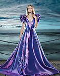 Young blond woman wearing a beautiful long blue dress, evening gown, at waterfront, artistic fashion portrait Image © MaximImages, License at https://www.maximimages.com