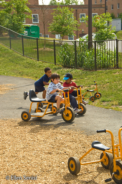 MR / College Park, Maryland.Center for Young Children, laboratory school within the College of Education at the University of Maryland. Full day developmental program of early childhood education for children of faculty, staff, and students at the university..Boys (left: 3, African-American; middle:4; right: 3) ride tricycles together on playground during recess..MR: Mai1 Ice1 Mcr1.© Ellen B. Senisi