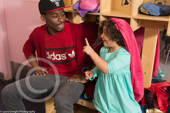Education Preschool 4 year olds young male teacher interacting with girl wearing dressup hat