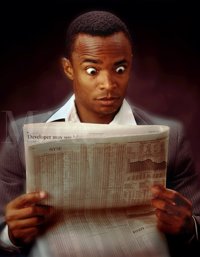 African American businessman reading the newspaper stock pages. stock market, investing, expressions, alarm, shock, surprise, black, man, men, male.