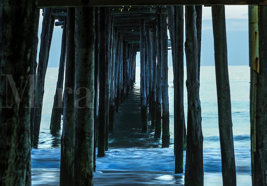 Ocean waves under a fishing pier,