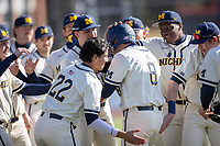 Michigan Wolverines first baseman Jimmy Obertop (8) is greeted by his teammates after hitting a home run during the NCAA baseball game against the Illinois Fighting Illini at Fisher Stadium on March 19, 2021 in Ann Arbor, Michigan. Illinois won the game 7-4. (Andrew Woolley/Four Seam Images)