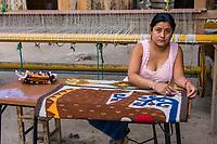 Santa Ana del Valle, Oaxaca, Mexico, North America.  Woman Working on Carpet with Jaguar Design.