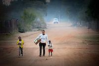 Una ragazza con i due figli cammina per le strade del villaggio di Sun City a 200 metri dal Royal Bafokeng Stadium di Rustenburg.USA Ghana 1-2 - USA vs Ghana 1-2.Ottavi di finale - Round of 16 matches.Campionati del Mondo di Calcio Sudafrica 2010 - World Cup South Africa 2010.Royal Bafokeng Stadium, Rustenburg, 26 / 06 / 2010.© Giorgio Perottino / Insidefoto .