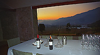 In the tasting room in the winery: a bottle of Altair and a bottle of Sideral on a table with a white table cloth. In the background, sunset over the Andes mountains., Bodega Altair in Region del Maule, Chile