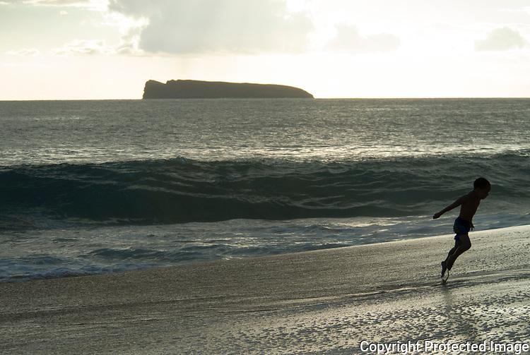 A kid running on the sandy shores of makena beach Maui Hawaii.