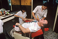 In Ho Chi Minh City, Saigon, February 1988. A veteran of Vietnam War, the american Bill Fero, wounded and amputed in 1971. Here, being shaved by a barber in the Rex Hotel.
