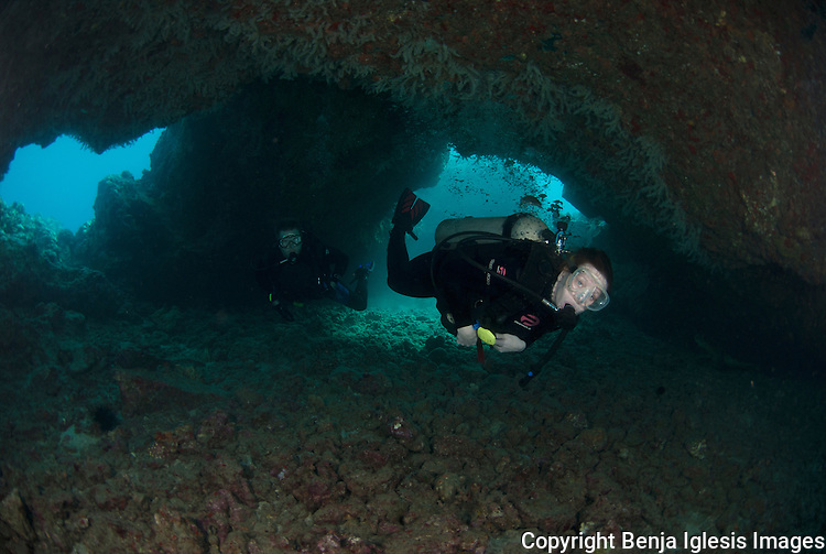 Divers inside cave at turtle town, Maui Hawaii.