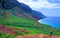 Hiker on the Kalalau trail looks toward a sliver of Kalalau beach glistening ahead