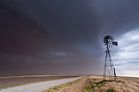 A thunderstorm produces a dust storm behind a windmill along a dirt road in  Amy, KS, June 2, 2012