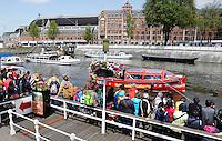 Amsterdam. Toeristen wachten op een rondvaartboot