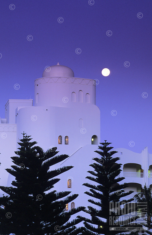 """Evening at the fabulous Kea Lani (Hawaiian: """"""""white heaven""""""""), in Wailea, Maui, with a beautiful full moon rising behind the opulent white towers of the hotel and the silhouettes of huge fir trees in the foreground."""