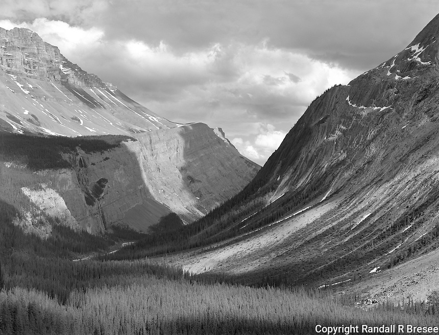 """""""North Saskatchewan River Valley"""" <br /> Banff National Park; Alberta, Canada<br /> <br /> The enormity of landscapes can be difficult to communicate in photographs. I tried to convey the immense size scale of the North Saskatchewan River Valley in this photo by maximizing image sharpness so the size of trees in the foreground could contrast with trees on both sides of the mountains above the valley. The huge size of this scene also is conveyed by the Icefields Parkway winding through the valley below. A dark yellow filter was used to reduce the atmospheric haze and make the mountains feel more """"solid."""""""