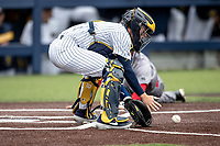 Michigan Wolverines catcher Joe Donovan (0) waits for a ball at the plate as Rutgers Scarlet Knights baserunner Kevin Blum (39) slides home on April 27, 2019 in the NCAA baseball game at Ray Fisher Stadium in Ann Arbor, Michigan. Michigan defeated Rutgers 10-1. (Andrew Woolley/Four Seam Images)