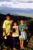 La Coipa, Peru. Three smiling girls, one holding a chicken, in the evening light.