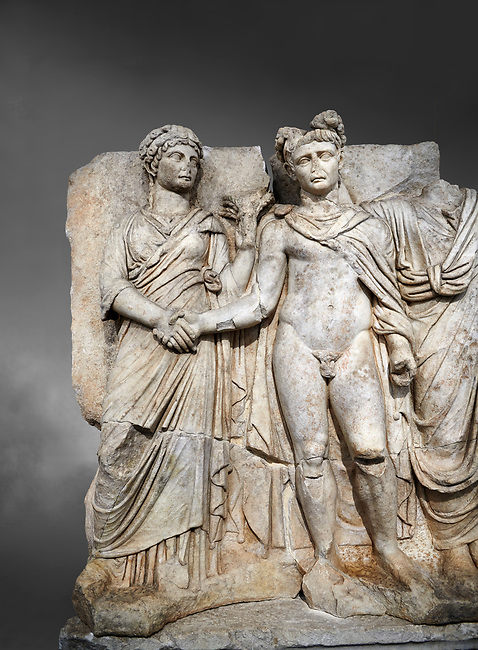 """Roman Sebasteion relief sculpture of emperor Claudius and Agrippina, Aphrodisias Museum, Aphrodisias, Turkey.  Against a grey background.<br /> <br /> Claudius in heroic nudity and military cloak shakes hands with his wife Agrippina and is crowned by the Roman people or the Senate wearing a toga. The subject is imperial concord with the traditional Roman state. Agrippina holds ears of wheat: like Demeter goddess of fertility. The emperor is crowned with an oak wreath, the Corona civica or """"citizen crow"""", awarded to Roman leaders for saving citizens lives: the emperor id therefore represented as saviour of the people."""