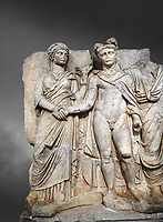 "Roman Sebasteion relief sculpture of emperor Claudius and Agrippina, Aphrodisias Museum, Aphrodisias, Turkey.  Against a grey background.<br /> <br /> Claudius in heroic nudity and military cloak shakes hands with his wife Agrippina and is crowned by the Roman people or the Senate wearing a toga. The subject is imperial concord with the traditional Roman state. Agrippina holds ears of wheat: like Demeter goddess of fertility. The emperor is crowned with an oak wreath, the Corona civica or ""citizen crow"", awarded to Roman leaders for saving citizens lives: the emperor id therefore represented as saviour of the people."