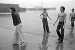 Scarborough teenagers on the beach Shrove Tuesday. There is a day off from school and the boys are catching local girls and throwing them into the sea. Yorkshire 1970s.