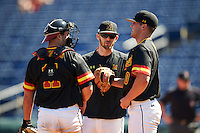 Maryland Terrapins coach Ryan Fecteau (center) talks with catcher Dan Maynard (11) and pitcher Mike Rescigno (40) during a game against the Alabama State Hornets on February 19, 2017 at Spectrum Field in Clearwater, Florida.  Maryland defeated Alabama State 9-7.  (Mike Janes/Four Seam Images)