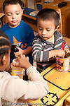 Education preschool 3-4 year olds group of two boys and a girl in kitchen area pretend play with food vertical