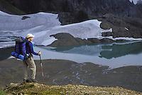 Hiker overlooking alpine lake and meadows, North Cascades, Cascade Mountains, Washington