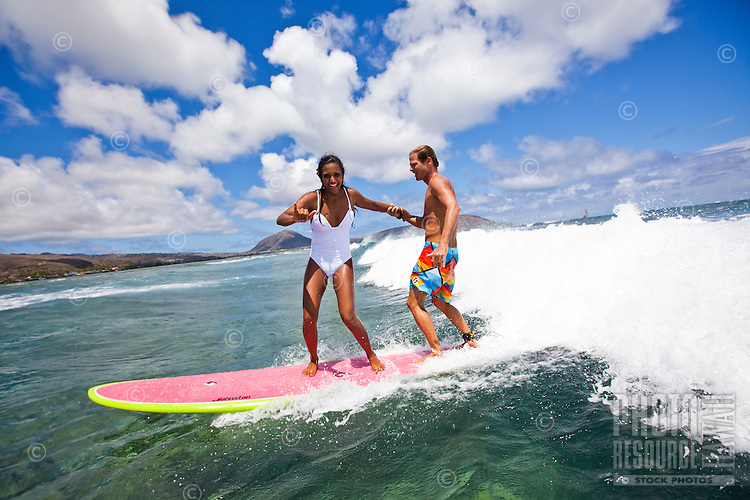Married couple tandem surfing on the south shore of Oahu
