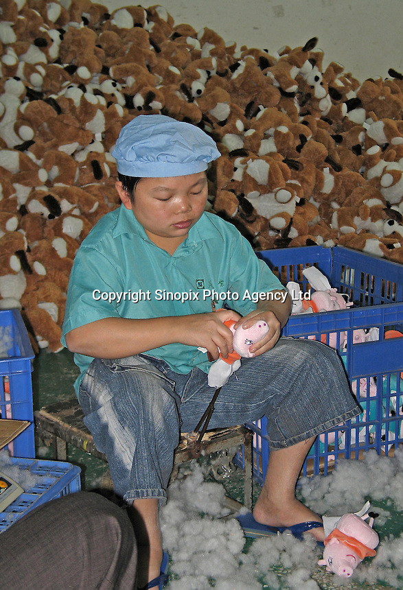 A sweat-shop style factory in an old district of Dongguan, China. The factory makes soft toys for many companies and biggest client is Wal-mart. In this photo a boy who appears under-age was stuffing animals at the factory..24 Nov 2004