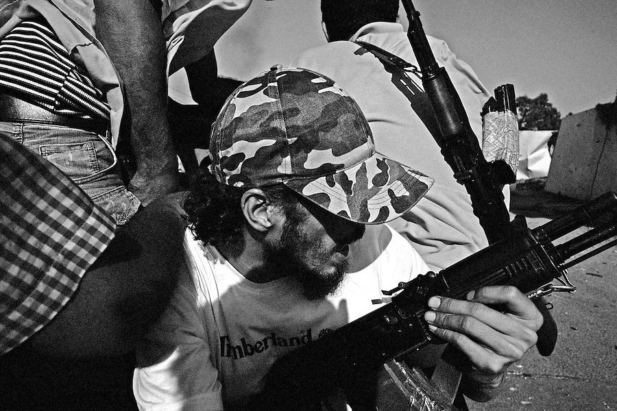 Rebel fighters in the rear of a pickup truck race towards the Bab Al Aziziya compound in Tripoli, Libya