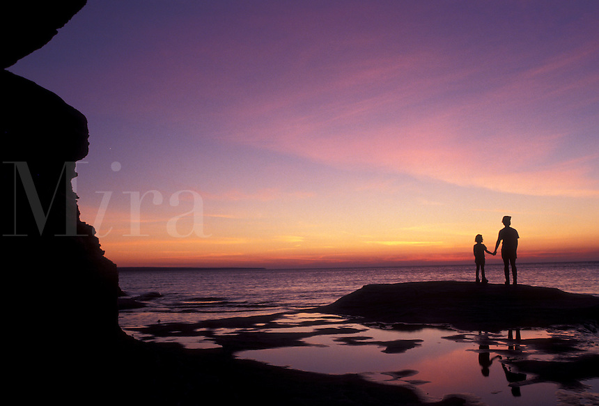 AJ2829, Pictured Rocks, Lake Superior, silhouette, sunset, sunrise, Upper Peninsula, U.P., Michigan, Mother and daughter standing holding hands on the edge of Lake Superior at sunset at Pictured Rocks National Lakeshore in Munising in the state of Michigan.