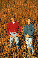 Farm couple in soybean field during autumn harvest.