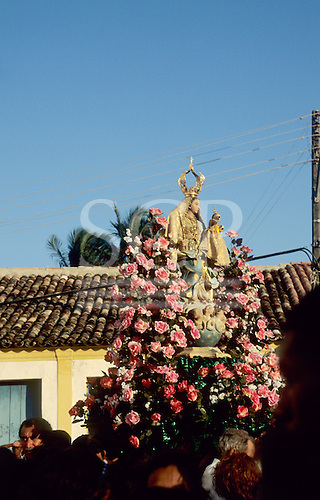 Arraial d'Ajuda, Brazil. Religious procession; the Blessed Virgin being carried atop a display of pink flowers. Bahia State.