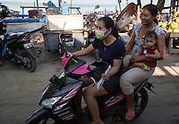 Bali, Indonesia.  Two Women and Small Girl on Motorbike, no Helmets, Jimbaran Fish Market.