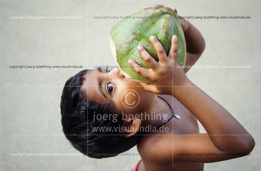 INDIEN Karnataka , Junge trinkt Kokoswasser aus einer Kokosnuss / INDIA Karnataka, child drinks coconut water at farm near Mangalore