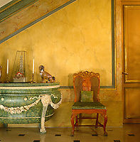 A Syrie Maugham green marble commode decorated with elaborate carved garlands complements the marbleised walls of the entrance hall