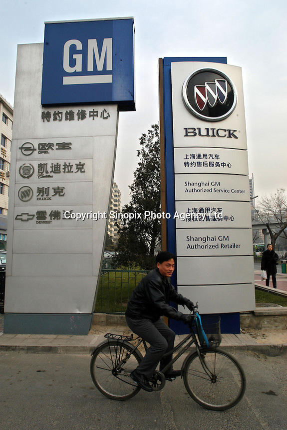 A man cycles pass the GM's Buick Service Centre in Beijing, China. SGM is a joint-venture between General Motors and the Shanghai Automotive Industry Corporation also known as SAIC..