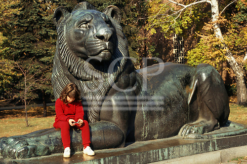 Sofia, Bulgaria. Girl in red sitting on the fore legs of the weeping lion statue at the tomb of the unknown soldier.