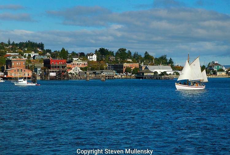 A Gaff rigged sailboat cruises Port Townsend Bay past the historic downtown waterfront area of Port Townsend, Washington on an early Autumn afternoon in 2005. Port Townsend is called the Dream City because so many dreams and hopes for the future were started here in the mid 19th century.